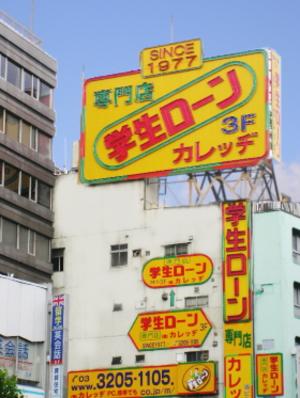 高田馬場駅前に目立つ学生ローン「カレッヂ」の看板・ビル